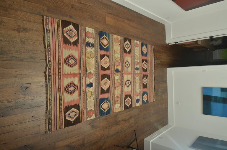 A flat-woven Kilim rug, hand women with vegetable dyes, banded hexagon designs of lozenges in pink, blue and ivory.