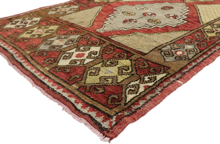 52403, vintage Turkish Oushak hallway runner with craftsman Tribal style. This hand knotted wool vintage Turkish Oushak runner features three stepped lozenge medallions floating on an abrashed field. Each medallion is dotted with a variety of