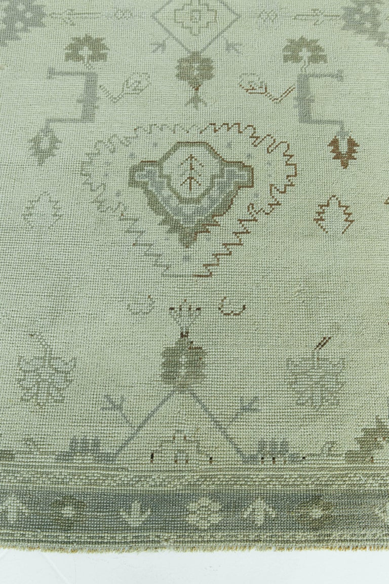 A vintage Turkish Oushak rug in ivory and taupe colors. This rug is unique for it's tribal motifs that a simple in design yet interesting for the viewer's eye. This rug will bring character to any space.   Rug number: 56559 Size: 4'10