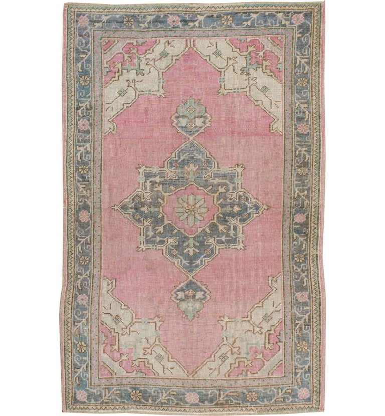 A vintage Turkish Oushak throw rug handmade during the mid-20th century with a dusty rose pink field and blue-grey octagram medallion and border.  Measures: 3' 7