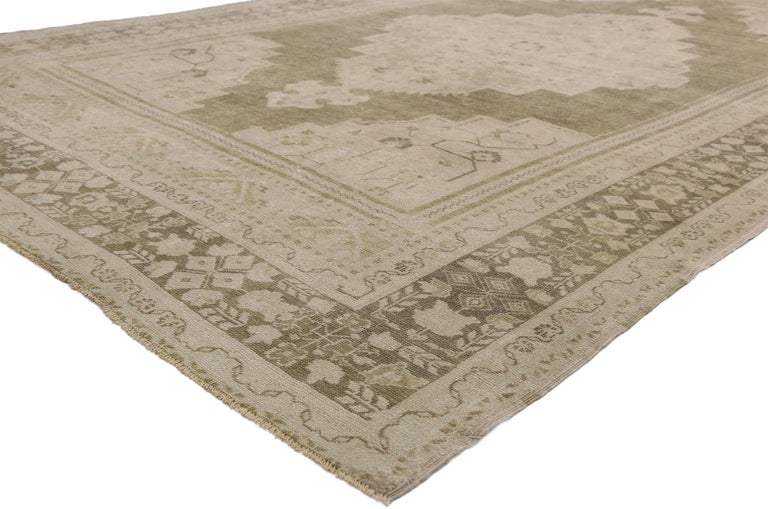 52488 vintage Turkish Oushak rug with Swedish Farmhouse and Cottage style. This daintily ornamented hand knotted wool vintage Turkish Oushak Rug features a large center medallion with anchor tip pendants floating in an open abrashed field. Angular