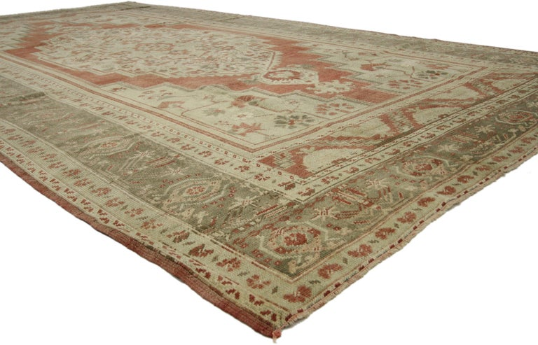51367 vintage Turkish Oushak rug with Tudor style. This hand knotted wool vintage Turkish Oushak rug features an oversized stepped hexagonal medallion with blooming palmette pendants floating in the center of an abrashed brick red field. Gorgeous