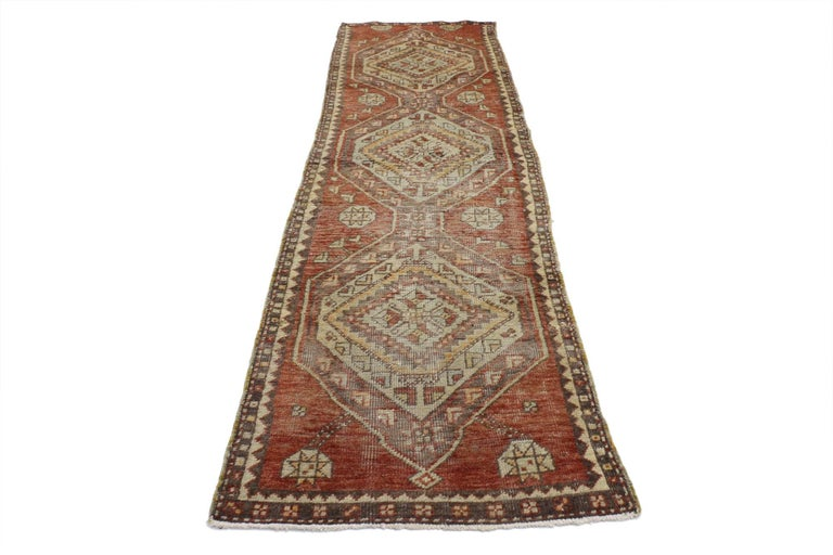 52087, vintage Turkish Oushak runner, narrow hallway runner. This hand knotted wool vintage Turkish Oushak runner features three connected hexagonal pole medallions spread across an abrashed brick red field. Superimposed concentric diamonds with