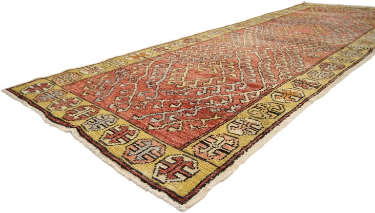 This hand-knotted wool vintage Turkish Oushak runner features a modern tribal style. The rich waves of abrash and eccentric design of this Oushak carpet runner showcase a highly decorative composition with time-softened colors. Rendered in