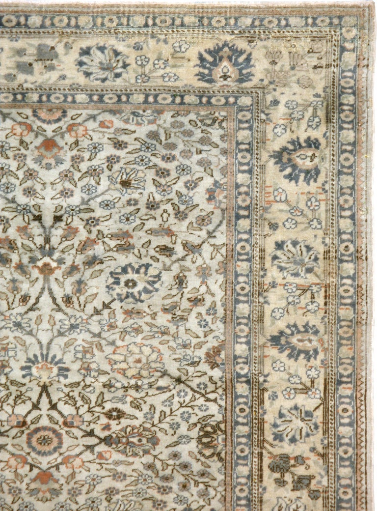 A vintage Turkish Sivas carpet from the mid-20th century. Thin vines and swirls of tiny leaves are the main ornamentations of the ivory ground of this eastern Turkish town rug. The straw yellow main border mixes erect and tilted palmettes with