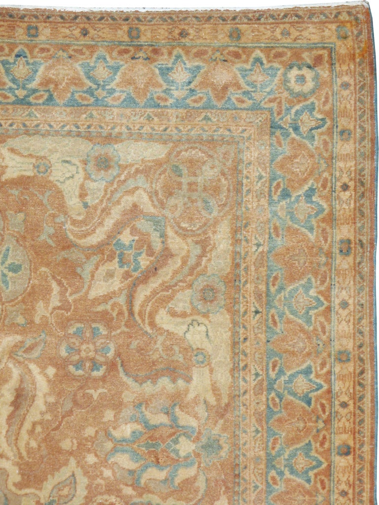 A vintage Turkish Sivas rug from the mid-20th century. This mellow colored Sivas has a medallion and bold leaf pattern on a light rust ground. The corners flow in a particularly dramatic manner in this accent rug sized perfectly for a coffee table