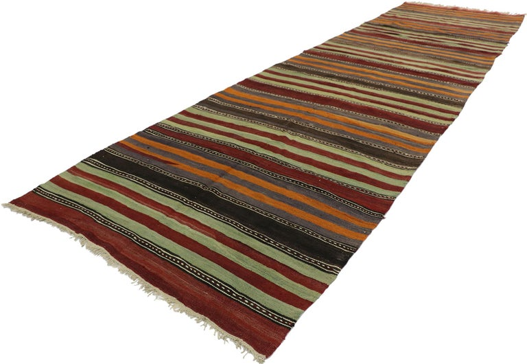 53129, vintage Turkish striped Kilim runner with modern cabin style. With its warm hues and rugged beauty, this hand-woven wool striped kilim runner manages to meld contemporary, modern, and traditional design elements. The flat-weave kilim rug