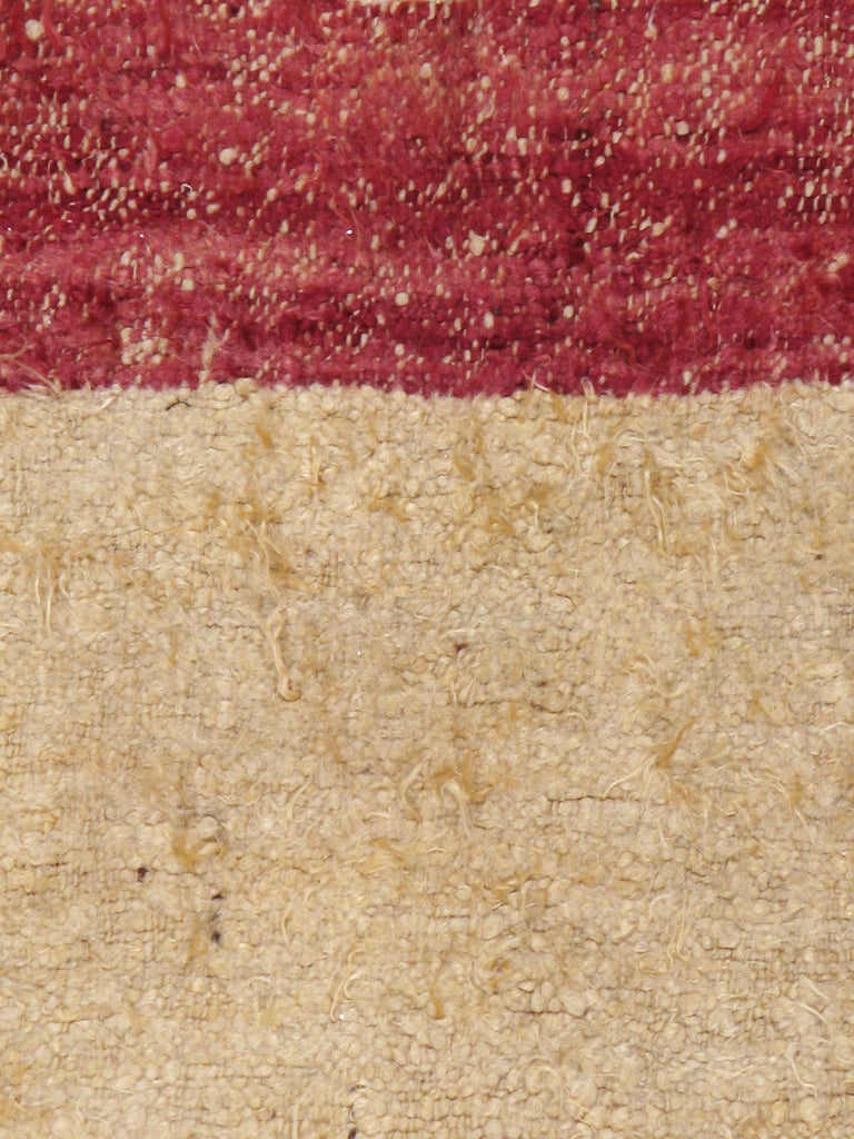 A vintage Tulu Turkish rug from the mid-20th century. A wide plain saturated marsala colored border with a beige open field. No ditzy ornamentation. Totally graphic with a very long pile. This is probably what rugs looked like thousands of years