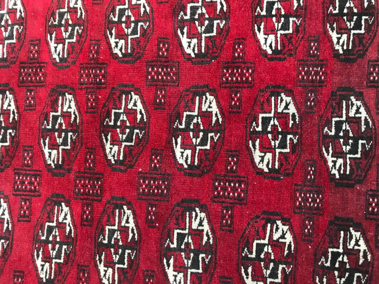 Beautiful 20th century Afghan rug with a Boukhara design in a red field, wool velvet on wool foundation.