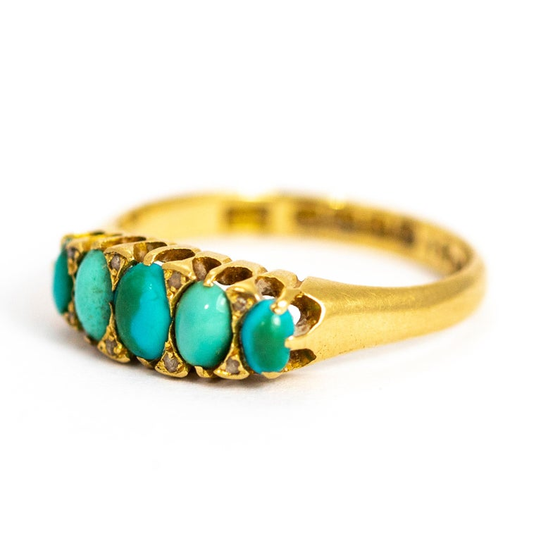 This wonderful turquoise five stone ring is modelled in 18ct gold and features eight small diamond points that sit between the oval turquoise stone cabochons. The band the stones sit ones quite chunky and very simple. Made in Birmingham, England.