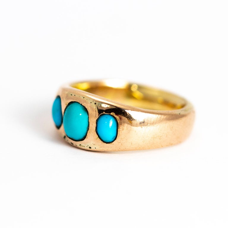The pop of the bright turquoise next to the glossy gold band makes the perfect pairing. The centre circular stone is slightly larger than the two smaller oval stones. The way the stones are set into this gold band give the ring a sort of lovely