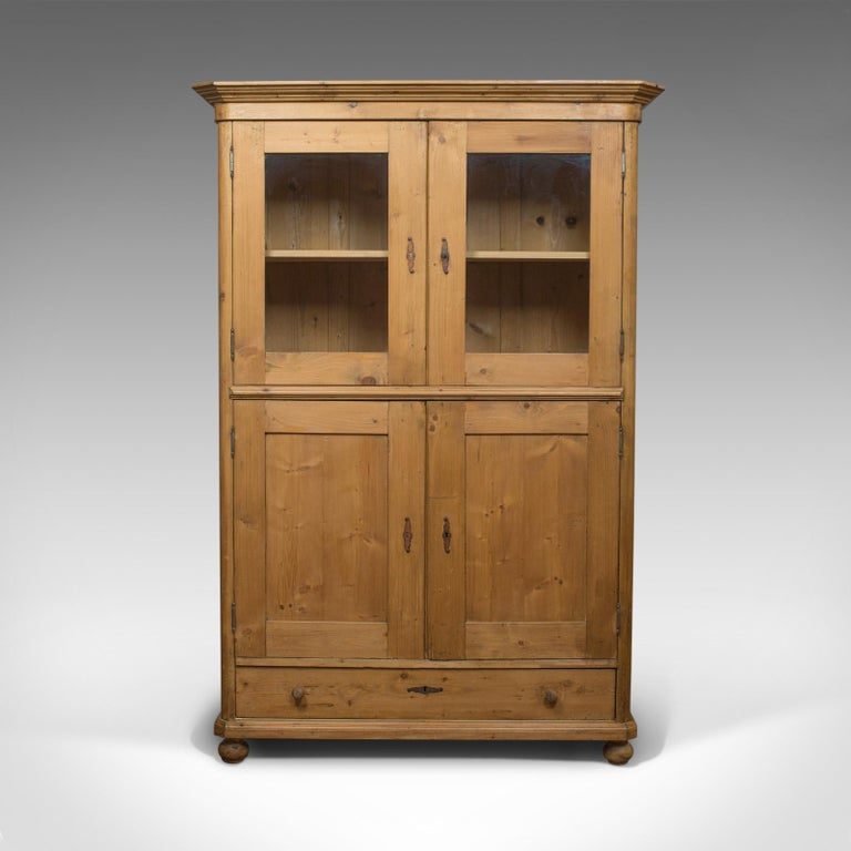 This is a vintage two-door bookcase cabinet. A French, pine cupboard dating to the mid-20th century, circa 1960.  Select pine displays rich biscuit hues and fine grain interest Good consistent color throughout and a desirable aged patina Deep