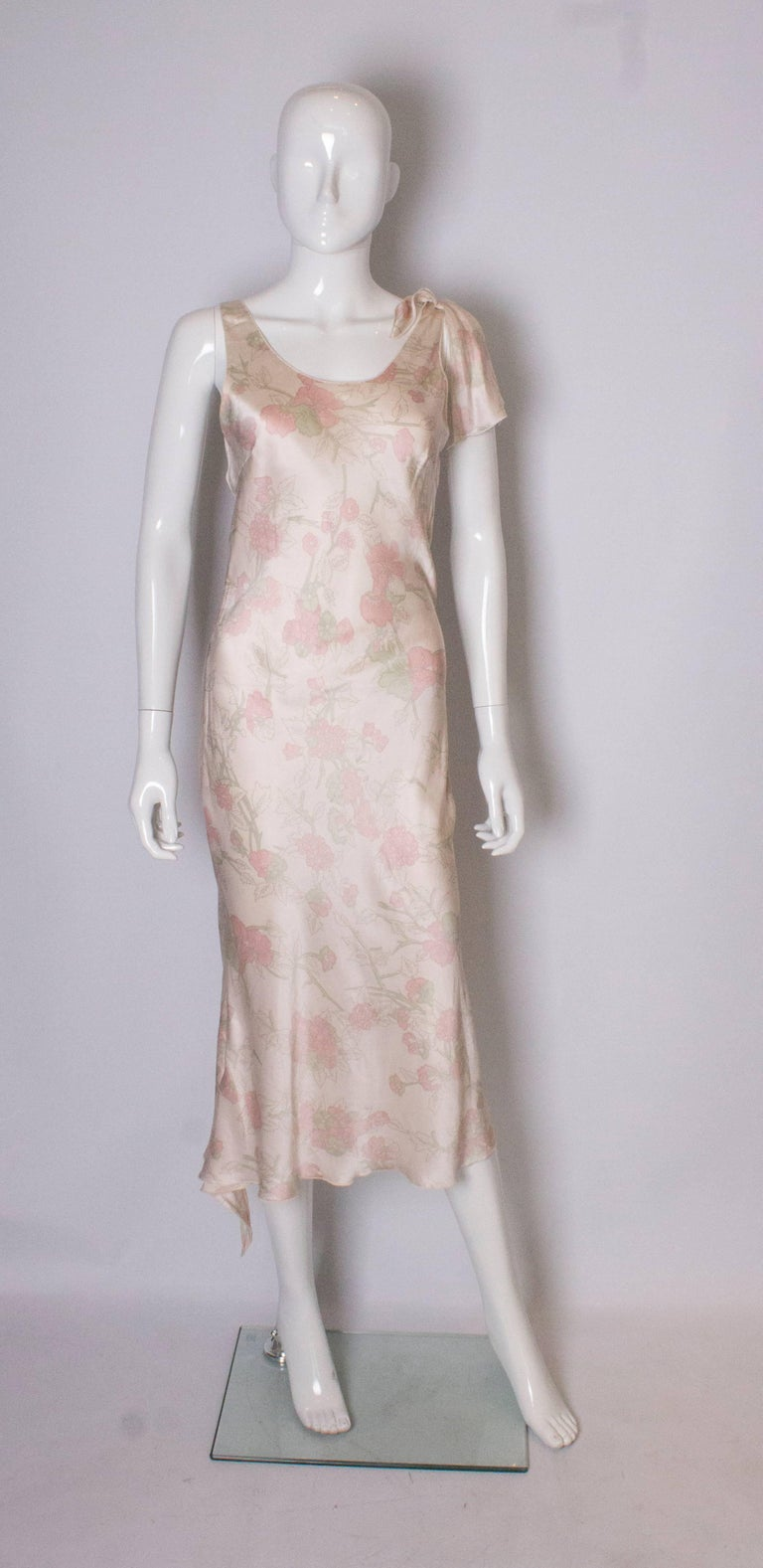 A pretty silk  slip dress or night dress by Ungaro. In a a pink floral print, the dress is bias cut and has a bow detail on one shoulder