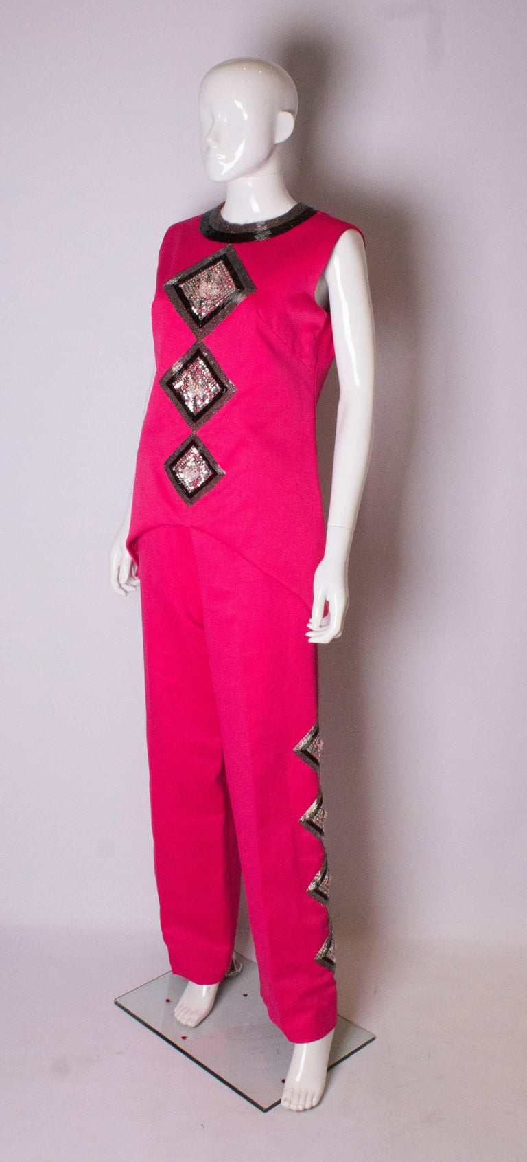 A chic vintage pink pantsuit by Valentina, number RN34438. The top has a round neckline with beading , is sleaveless and has a 10'' slit on either side. It had wonderful bead and sequin decoration on the front , is fully lined and has a central back