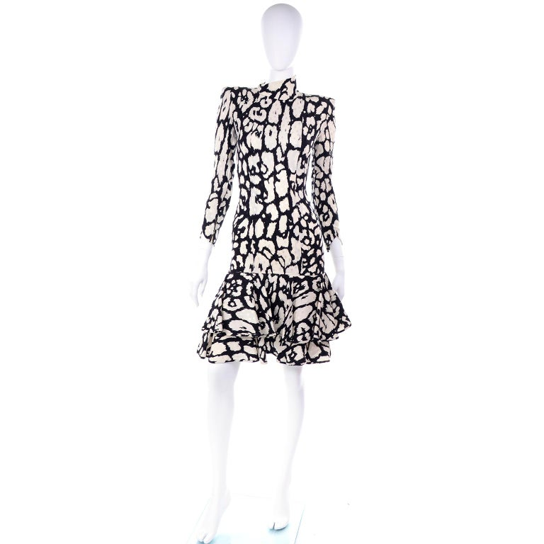 This is a gorgeous vintage Valentino Boutique dress in an abstract black print on light cream silk with tonal white dots.  This fully lined silk dress has a ruffled flounce hemline, shoulder pads and angled notched sleeve cuffs.  The dress has an