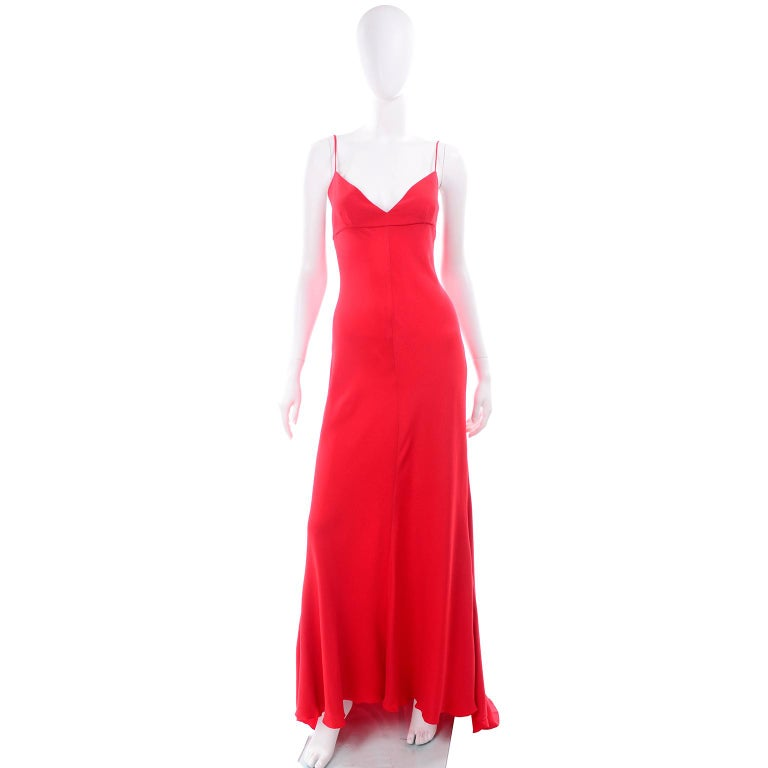 This is an absolutely gorgeous Valentino red vintage slip dress. This beautiful silk evening gown has spaghetti straps, an empire waist, and closes with a metal zipper and hook and eye on that center back seam. The dress has a slight train and is