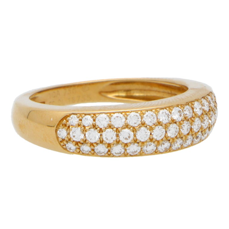 A beautiful vintage Van Cleef & Arpels diamond band ring set in 18k yellow gold.   The ring is comprised of three rows of round brilliant cut diamonds which are pavé set in a subtle bombé design. The shoulders of the band graduate elegantly round to
