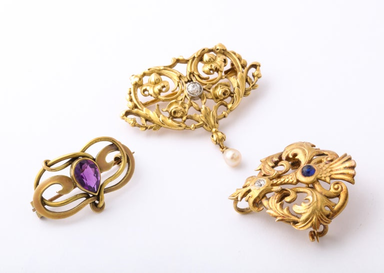 Three various brooches, all with the finest gold work from the early 1900's, are from the far right, a Rikers brooch in 14 Kt with a sapphire and diamond. Rikers is a highly reputed jewelry firm from Newark that made jewelry when the American