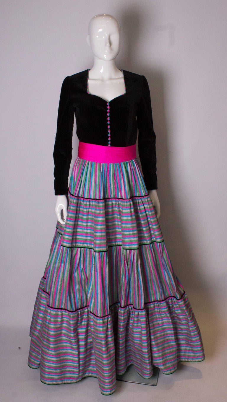 A great vintage gown by Regamus London. The gown has a black velvet top half with a sweetheart neckline. It has a full skirt, with silk tiers of horizontal and vertical stripe silk. It has a net underskirt which is edged in coloured silk, and a