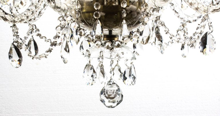 This is a beautiful vintage Venetian style two-tier crystal chandelier with 12 lights and beautiful clear crystal drops, dating from the second half of the 20th century.  There are four lights on the top tier and eight on the lower tier.  It is