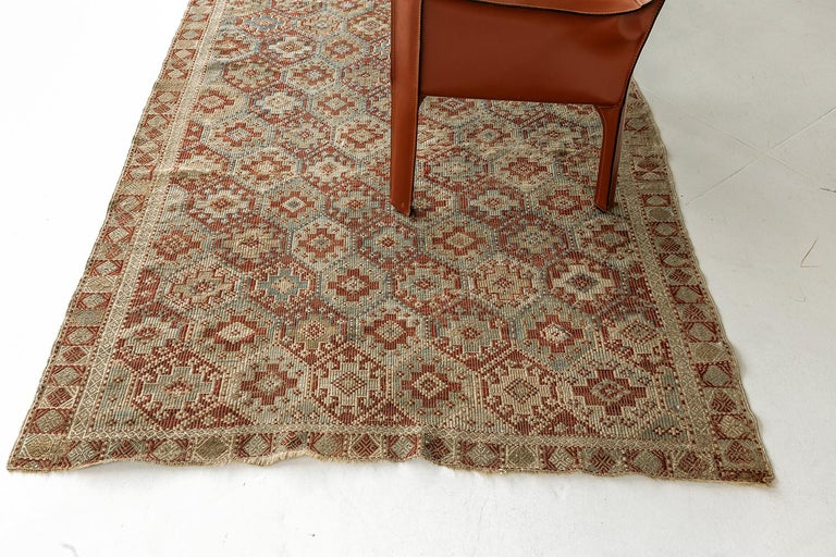 A timeless piece that is designed to captivate one's stylish mind. Featuring this Vintage Verneh Flat Weave Kilim rug that displays repeated motifs of cruciform tiles with lozenge patterns inside in alternating colors of burnt orange, turquoise, sky