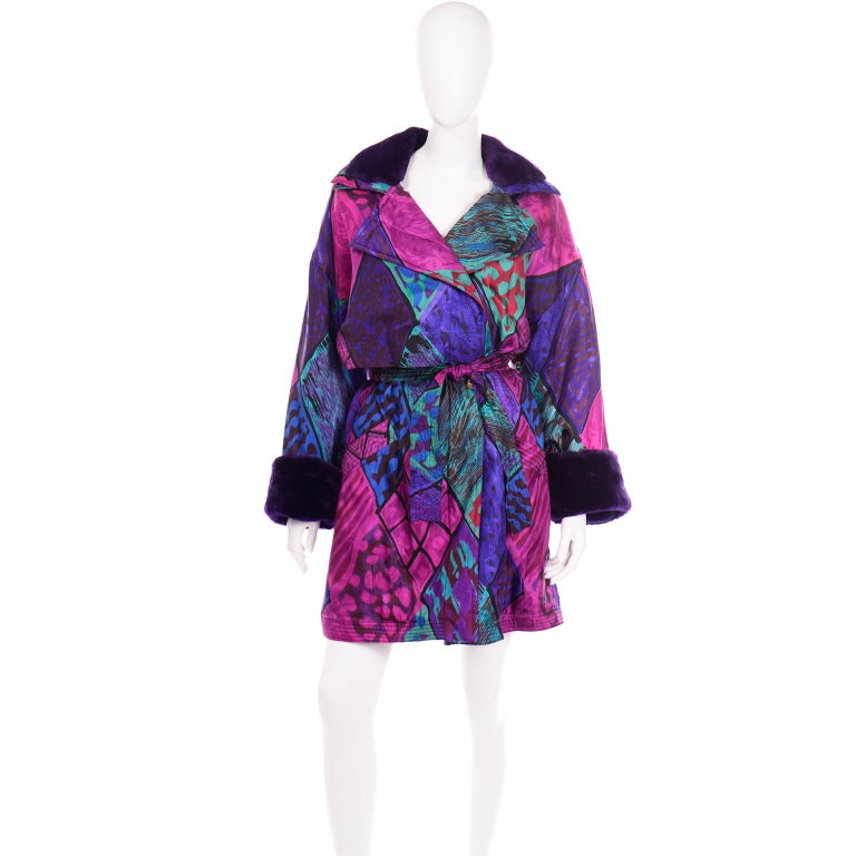 This vintage Versace Sport coat is simply gorgeous and we love the colorful silk fabric with purple faux fur collar and cuffs. The colors of the abstract silk print consist of purple, magenta, burgundy, green, teal, blue, and black. This coat has