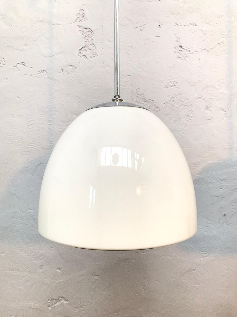 Vintage Danish Vilhelm Lauritzen for Louis Poulsen opaline glass bell shaped pendant chandeliers. In original condition with new wiring and grounded. Hanging on a 60cm long nickel-plated copper pipe that can be shortened and rethreaded if so