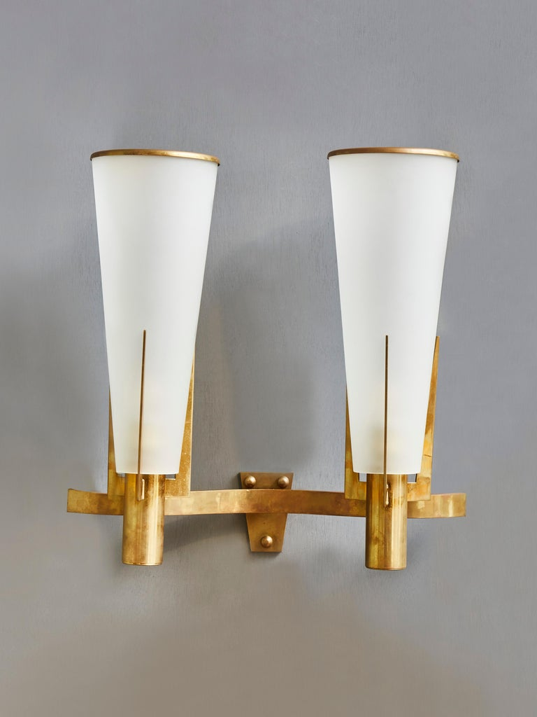 Elegant pair of vintage wall sconces made of brass and opaline glass. Designed by Stilnovo.  2 light bulbs.  Italy, 1960s.