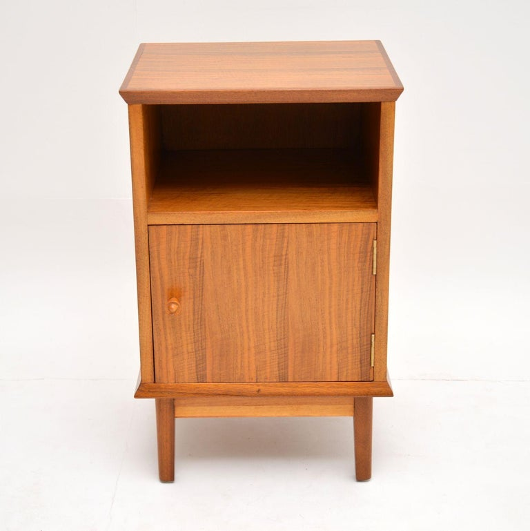 A stylish little bedside cabinet in walnut, this was made by the high end manufacturer Alfred COX. It was made in Britain and dates from the 1950s-1960s. We have had this stripped and re-polished to a very high standard, the condition is excellent