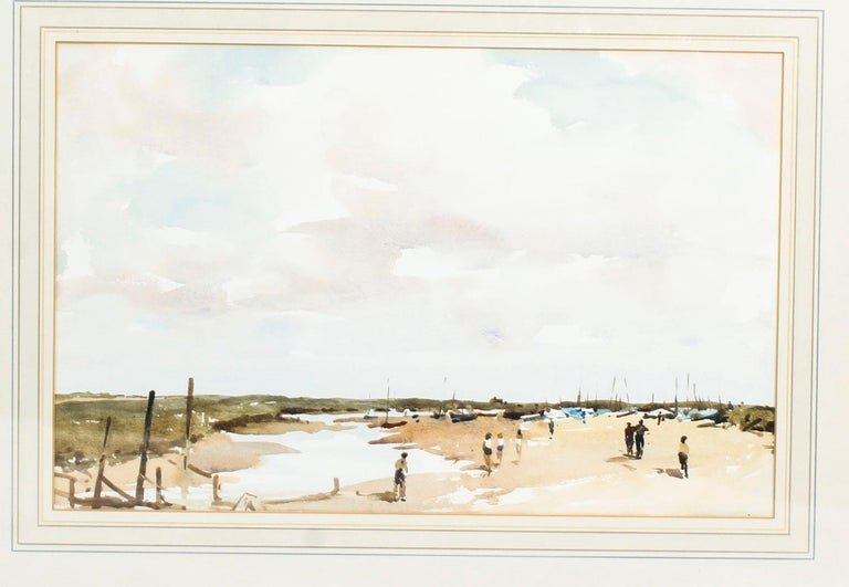 Vintage English watercolor landscape by Edward Wesson British, (1910-1983), circa 1960 in date.  This wonderful watercolor features a tranquil landscape of an English beach scene with figures walking and boats in the background.  This watercolor