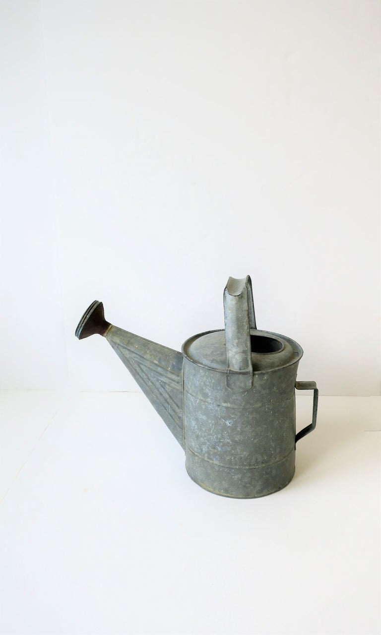A vintage - antique metal watering can, circa early 20th century.