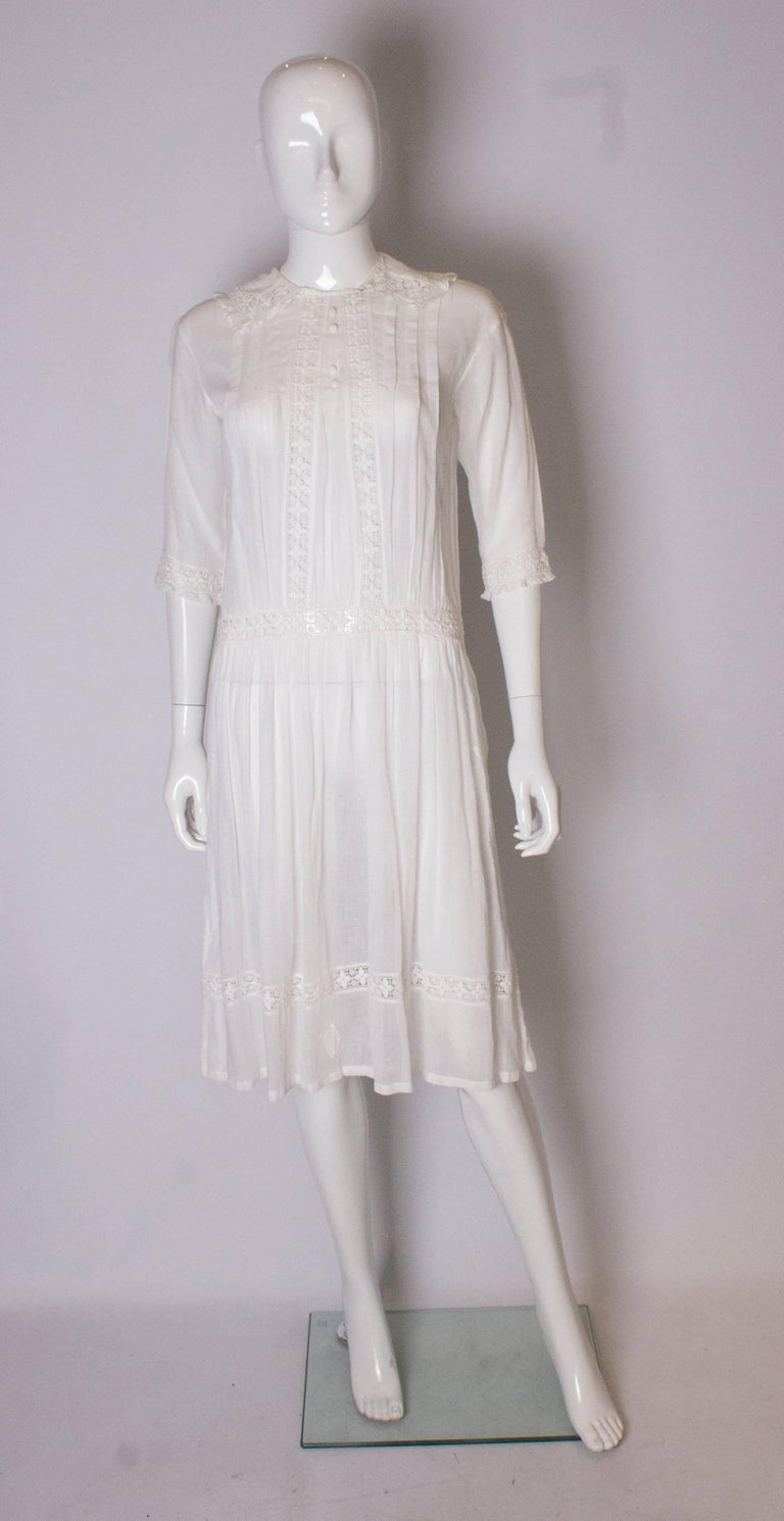 A pretty vintage edwardian white cotton dress . The dress has lace detail on the the cuffs and collar, with pleats on the front.  It has elbow length sleeves with lace detail.