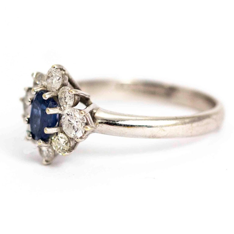 A superb vintage cluster ring with a central sapphire surrounded by eight white round cut diamonds. The oval sapphire has wonderful colour and measures approximately 45 points. The total diamonds weight in this ring measures approximately 82 points.