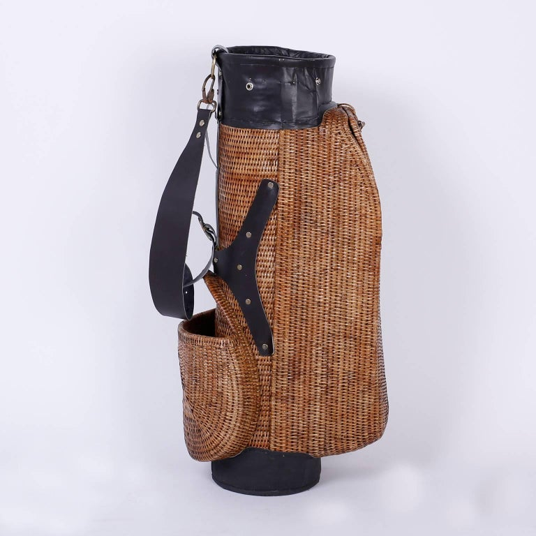 Vintage wicker golf bag with leather straps, top and foot. Having two storage