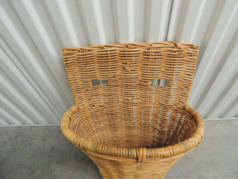 Vintage wicker and bamboo woven wall basket or umbrella stand. Oval conical shape wall basket with openings woven in the back to hang on the wall. Size: 16 x 12 x 24 H.