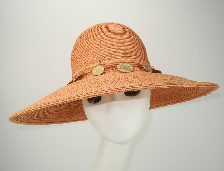 1980's wide brim hat in a cantaloupe orange straw (light enough to be neutral) accented by faux Spanish gold coins.  The inner rim is trimmed in a hot pink grosgrain ribbon.  Perfect for adding a chic style to beach wear or summertime casuals.  No