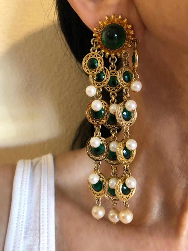 Beautiful pair of faux emerald and pearl earrings by William de Lillo. The statement clip-on earrings are comprised of highly detailed gold-tone circular beads which are accented in the center by faux glass emeralds - the chains and segments are