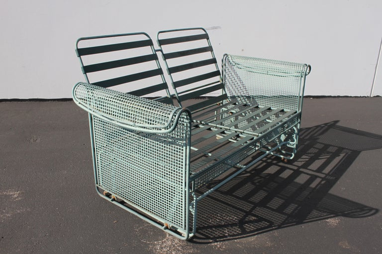 Vintage Woodard patio set with both rocking glider-settee and armchair, coffee table and side table. Shown with faded original green paint and grid / mesh pattern sides reminiscent of the metal work of architect Josef Hoffmann for Wiener Werkstätte.