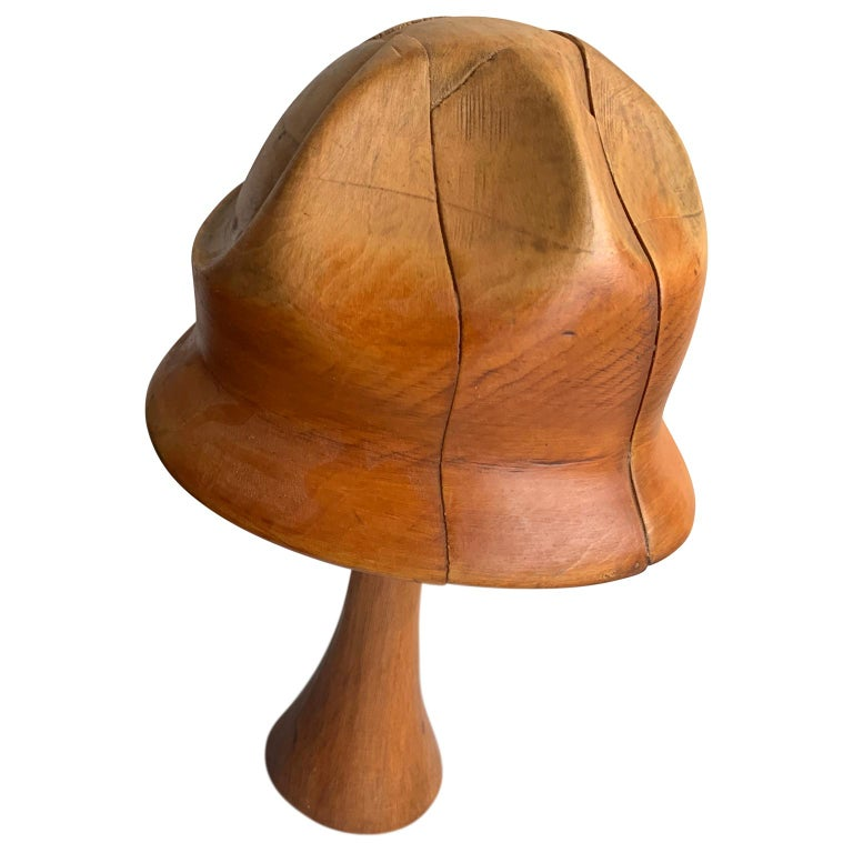 Vintage Wooden Hat Mold The hat mold is displayed on a wooden stand