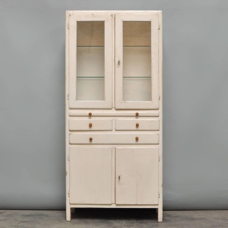 Medical cabinet from the 1940s with the original antique glass and locks. Used in a former hospital in Budapest. The two glass plates are new.