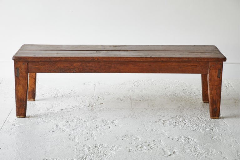 Vintage wooden rectangular coffee table that can also work as a bench. The top is comprised of two planks.