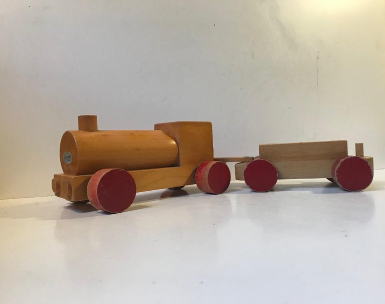Vintage train or locomotive set made from partially lacquered and painted beechwood. This item surely has been loved and played with for decades and it show in the most charming way. It was designed by Kay Bojesen and manufactured in his own