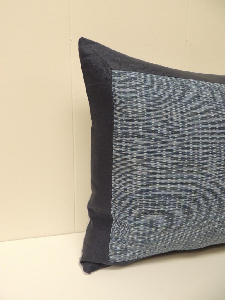 Vintage woven blue and white Ikat textile bolster decorative pillow, framed with navy blue linen and texture gris linen backing.