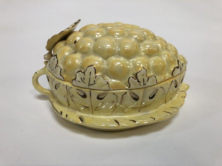 This vintage covered dish is made out of porcelain ceramic. It depicts bright yellow grapes with green-tinted grape leaves, hand-painted with gold veins and finished with a lusterware glaze.  This lusterware grapes box was made by Sasha in the USA