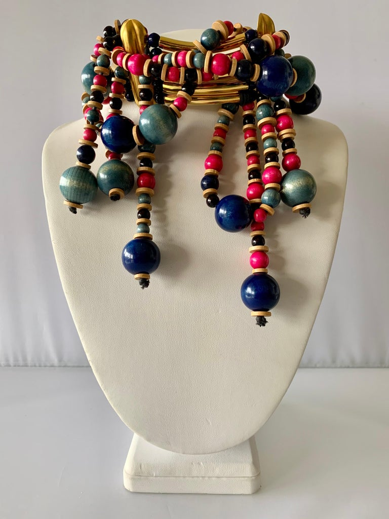 Exquisite and rare find! Vintage Yves Saint Laurent Haute Couture tribal statement necklace/choker, comprised out of long architectural gilt metal tube beads and round wooden beads in; blue, pink, and turquoise. The beads wrap around the entire
