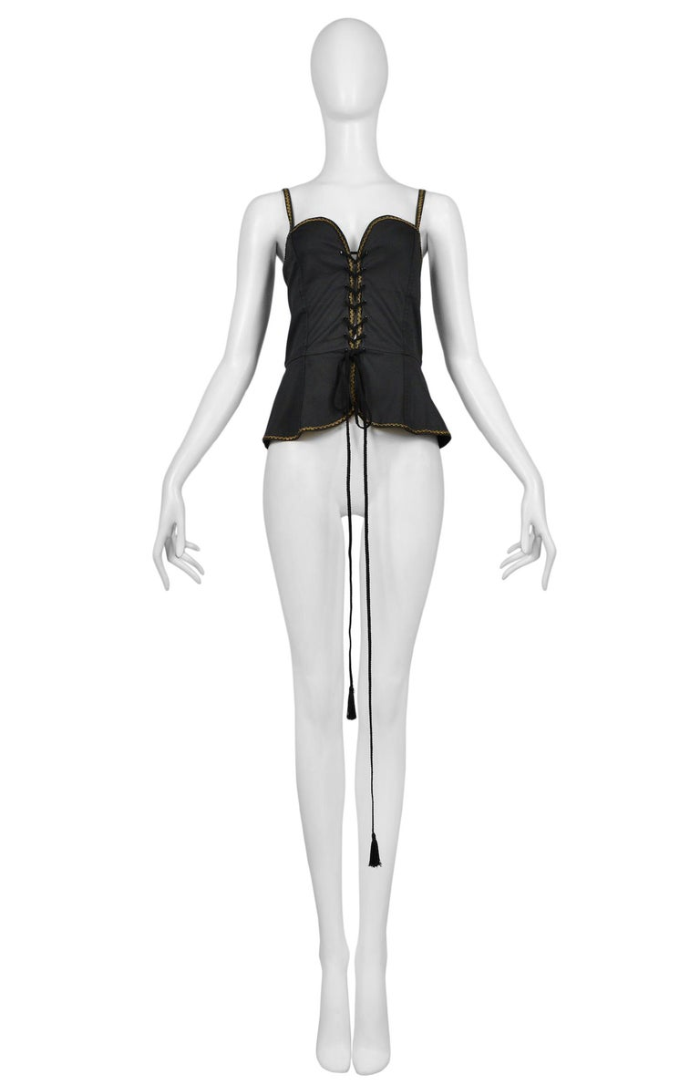 Vintage Yves Saint Laurent black cotton corset top featuring a built-in peplum, gold rickrack trim along the edges and spaghetti straps, and tassel cording lacing at front. Circa 1977.  Excellent Vintage Condition.  Size 38