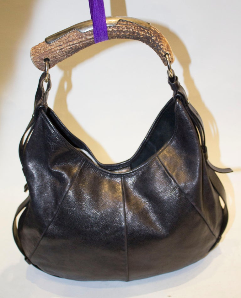 A chic YSL black leather mombasa hobo bag , with a horn handle and adjustable strap The bag has a popper fastening and internal zip pocket. Measurements width 16'', height 12'' depth 1''