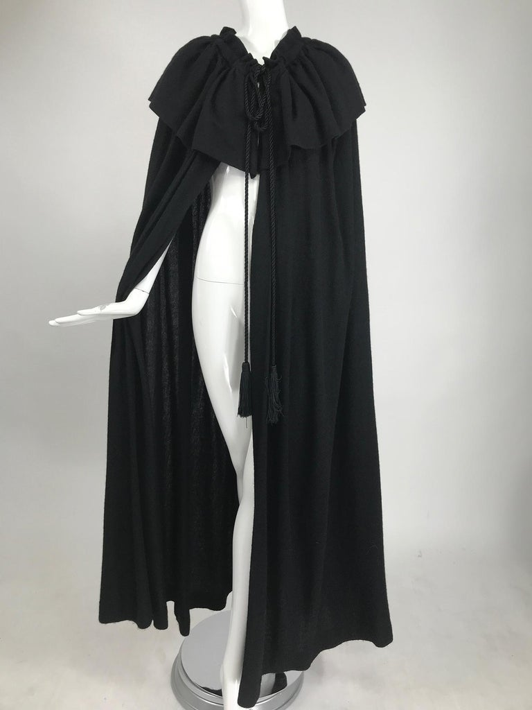 Vintage Yves Saint Laurent, Rive Gauche black wool cape from the 1970s. Lightweight  black wool cape with long silky black tassel end neck ties The ties run through the neck casing and can gather the neck in.  A narrow gathered collar has a deep