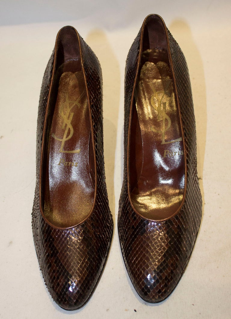 A chic pair of vintage Yves Saint Laurent Paris shoes in brown and black snakeskin.  The shoes are style 84327, in a size 81 /2 M , with heel height 3 1/2''