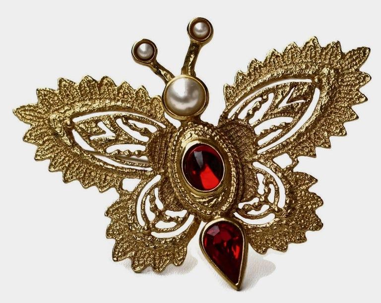 Vintage YVES SAINT LAURENT Butterfly Brooch by Robert Goossens  Measurements: Height: 6 cms Width: 8 cms  Features: - 100% Authentic YVES SAINT LAURENT. - Intricate gilt metal hardware in gold tone. - Embellished with Faux Pearls (very minor